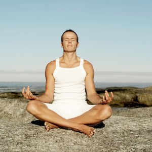 Man Meditating on a Rock at the Beach